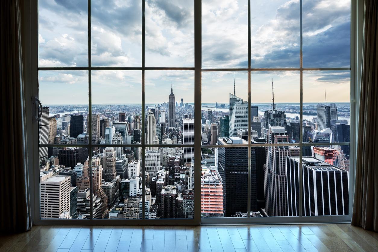 von einem Wohnungsfenster aus auf Immobilien in Manhattan blicken