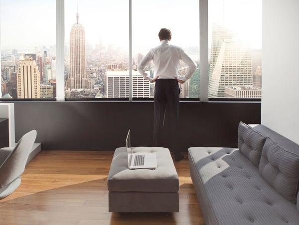 ein junger Mann in seiner Luxuswohnung mit Blick auf die Skyline von New York