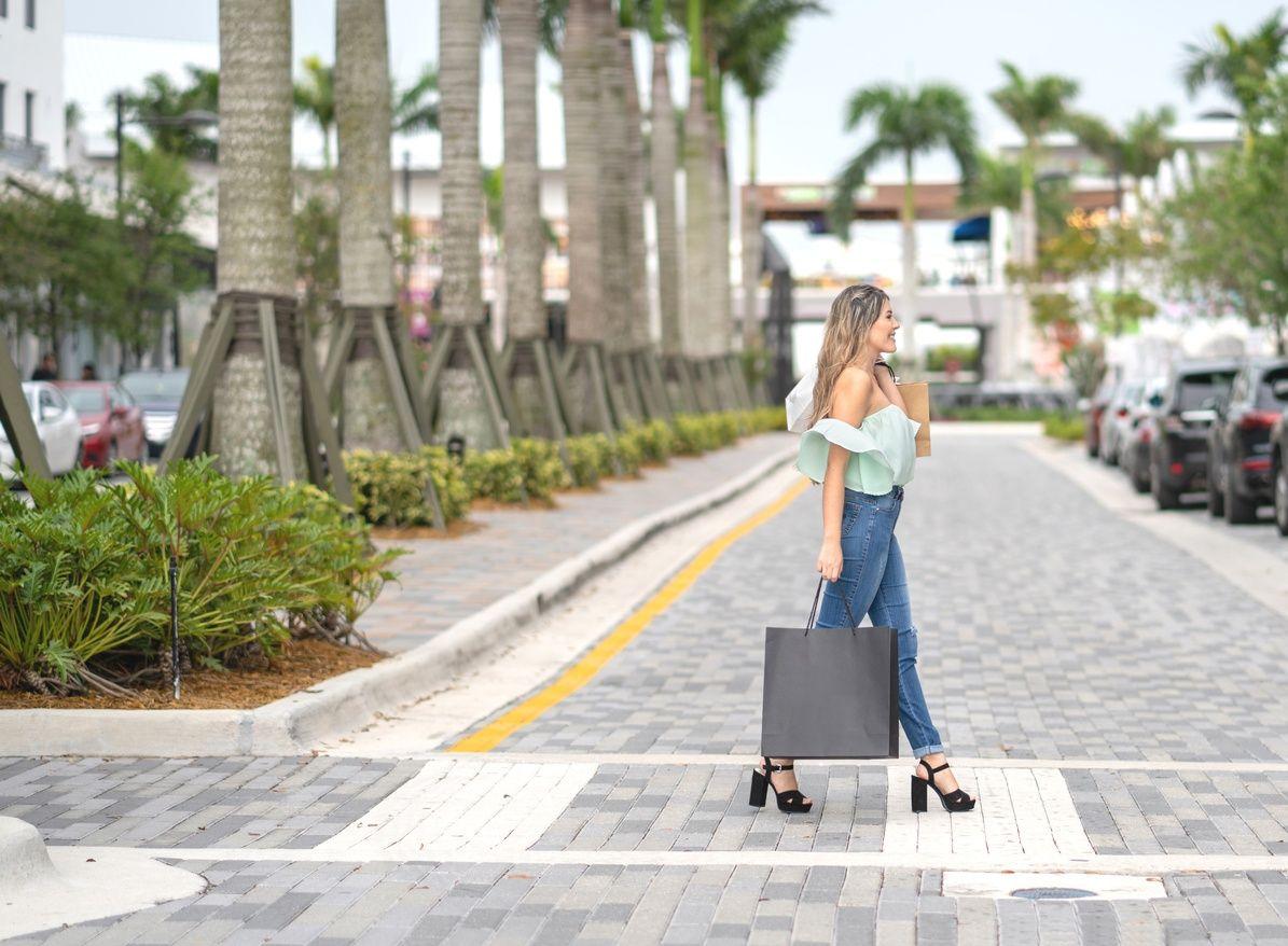 Frau, die in Coral Gables eine Einkaufstasche hält und die Straße überquert